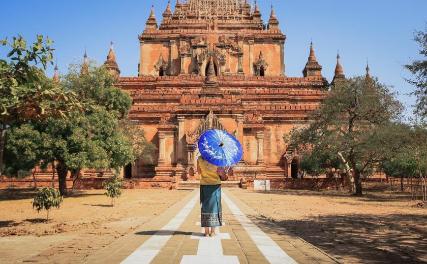 Femme birmane de dos en tenue traditionnelle devant un temple sur le site de Bagan