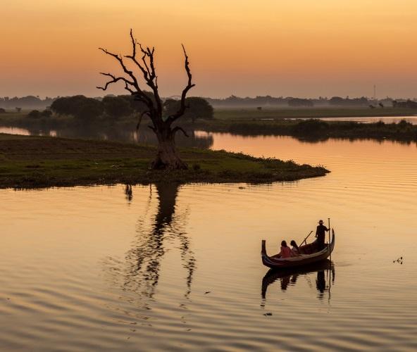 Bateau traversant le lac de Taunghaman au coucher de soleil